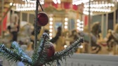 christmas tree ornament : Festive atmosphere. People ride on the carousel. In the evening, during a snowfall. Stock Footage