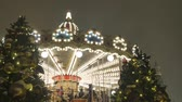 Festive atmosphere. People ride on the carousel. In the evening, during a snowfall. Стоковые видеозаписи