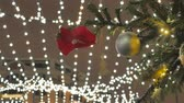 Christmas tree covered with snow, it is decorated with balls and toys. On the street, there is a blizzard. In the background, the festive decoration of the city is out of focus. Stock Footage
