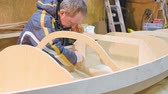 Male hands closeup. He handles the seams of the boat with epoxy glue for tightness. The boat is made by hand. Stock Footage