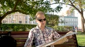 ninhada : Caucasian man with glasses sitting in park on bench laying out map of city Stock Footage