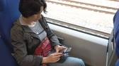 a woman sits by the window of a train Holding a smartphone