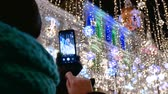 Outdoor Caucasian woman takes photo of New Year garland. View from the back. Stock Footage