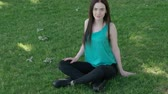 casual : Calm young girl sitting crossed legs on grass  UHD footage Stock Footage