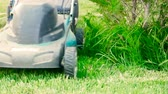 zahradník : Astrakhan, Russia, 27 of May 2018: Makita-brand Lawnmower at work. Lawn mower cutting green grass in backyard. Gardening background. Dostupné videozáznamy