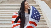 immigrants : Brunette woman warapped in US flag posing in front of stairs leading up, immigration from latino country concept Stock Footage