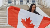 immigrants : Brunette girl with Canada Flag in Her Hands Smiling posing Outdoors in Autumn Time. Immigrant Activist. Stock Footage