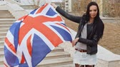 immigrants : Immigrant patriotic activist. Latino girl with waving Great Britain Union Jack flag in hands looking at camera and smiling FHD footage Stock Footage
