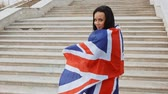 immigrants : Happy woman wrapped in union jack flag in front of stairs leading upwards, immigration concept