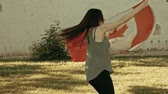 elation : Girl dancing with Canada nation flag in slow-motion
