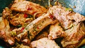 cast : Pork ribs with spices in the frying pan closeup