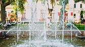 felhasználatlan : Park Fountain in slow motion with unrecognizable senior people walking on blurred background Stock mozgókép