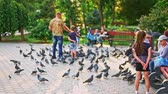 feathering : Astrakhan, Russia circa september 2018: Girl running after pigeons. Girl playing with pigeons in city park.