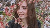 веточка : Girl with freckles posing in windy weather in orchard near the blooming cherry tree
