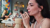 Girl drink latte coffe from straw profile side view Stok Video