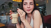 Serious girl drinks coffee in hipster caffeteria dutch angle shot Wideo