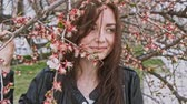 Smiling girl in park posing near cherry tree in bloom Stok Video