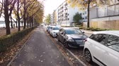 gyalogút : Bonn Germany, 06 November 2019: many cars parked on both sides of sidewalk of Rhine embankment 4k 50fps clip