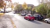 gyalogút : Bonn Germany, 06 November 2019: small red car riding in the street while many cars parked on sidewalk of Rhine embankment 4k 50fps clip