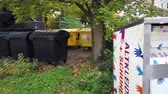 çöp : Bonn Germany, 10 November 2019: Line of garbage dumpsters near students dorm. Garbage dumpsters in a residential area 4k 50fps clip