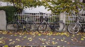 kozmopolita : Bonn Germany, 10 November 2019: Bicycles parked leaning the fence along the sidewalk 4k 50fps. Stock mozgókép