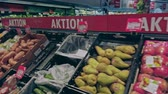 középkorú : Bonn, Germany - 14 of Dec., 2019: interior shot of REWE supermarket in Bonn POV view. Shelves with fruit on sale 4k 60 fps slow motion Stock mozgókép