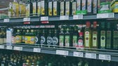 comestível : Bonn, Germany - 14 of Dec., 2019: interior shot of REWE supermarket in Bonn POV view. Many types of vegetable oil stands on the shelves - coconut, rapeseed, pumpkin and others 4k