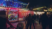 rodas : Bonn Germany, 23 Dec 2019: People walk at the Christmas market with a carousel 4k slow motion