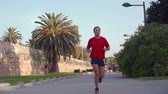 antreman : Man in a red t-shirt running in the park. Active lifestyle. Fitness outdoor activities. Runner in Valencian River Turia park.