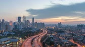 real jam : Majestic and beautiful day to night sunset time lapse at Kuala Lumpur city skyline. Showing sky changing colors and light trail from traffic on the road lead to the city. pan right
