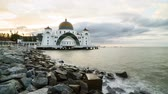 Time lapse 4k Footage of Beautiful Sunrise At Melaka Straits Floating Mosque, or Masjid Selat Melaka with dramatic cloudy sky. Pan right