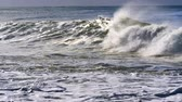 stijgende lijn : Waves breaking near shore, with the sun shining on them