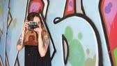 Girl with tattoo and vintage camera stand near the graffiti wall. Dostupné videozáznamy