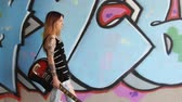 Girl with electric guitar walking along the graffiti wall. Dostupné videozáznamy