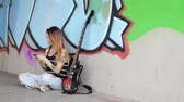 Girl sitting near graffiti wall with a guitar listening music.