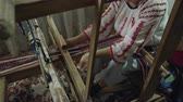 népi : A hand-held medium shot of weaver who is weaving a traditional belt on a obsolete wooden weaving machine.
