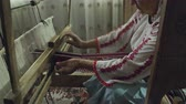 telar : A dolly out shot of weaver who is weaving a traditional belt on a obsolete wooden weaving machine. Archivo de Video