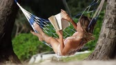 sayfa : Young lady reading a book in a swinging hammock in a garden