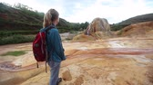 atrações : Lady with backpack watching on Analavory geysers. Republic of Madagascar.