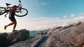 fitness : Man runs with bicycle on the rocky terrain