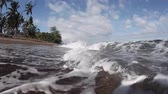rega : Tropical beach with dark sand and sea waves splash on the camera
