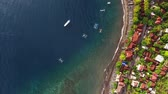 ниже : Aerial shoot of underwater coral reef near shore with buildings. Bali, Indonesia