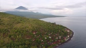 transparente : Aerial shoot of calm lagoon with buildings on the shore and volcano on the horizon. Bali, Indonesia