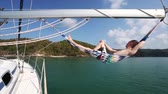 linha do horizonte : Young man relaxing in the hammock set on the sail boat while sailing in the sea