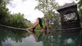 joga : Young woman stretches and performs yoga in the green graden by the pool Wideo