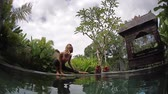 meditar : Young woman stretches and performs yoga exercises in the green graden by the pool