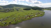 деревня : Aerial view of a meadow with lots of tents, cars and buildingds. Outdoor music festival on coast of a lake Стоковые видеозаписи