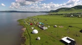 venkov : Aerial view of a meadow with lots of tents, cars and buildingds. Outdoor music festival on coast of a lake Dostupné videozáznamy