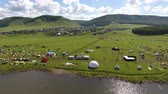 vila : Aerial view of a meadow with lots of tents, cars and buildingds. Outdoor music festival on coast of a lake Vídeos