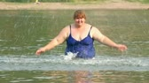 river : woman with overweight bath in river